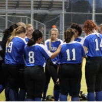 Softball team meeting in a huddle