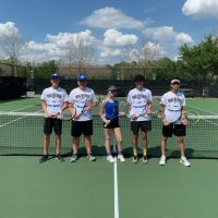 5 students pose with tennis rackets on a tennis court